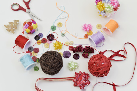 high-angle shot of some handmade christmas balls, made with ribbon bow, strings and buttons of different colors, and a pile of different haberdashery items on a white table