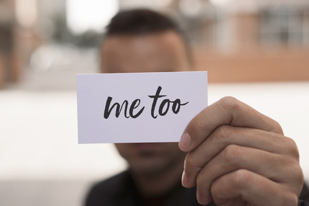 closeup of a young caucasian man in the street showing a piece of paper with the text me too written in it