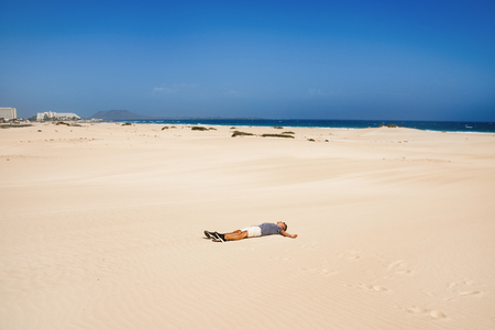 a young caucasian man wearing a t-shirt and shorts lies with his arms open on the white sand of the dunes of Corralejo in Fuerteventura, Canary Islands, Spain
