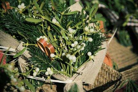 closeup of some bouquets of mistletoe wrapped in a rustic fabric on sale in a christmas market in Barcelona, Spain