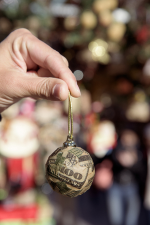 closeup of a young man holding a christmas ball wrapped on pieces of a US 100 dollar bill in a christmas market