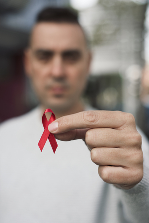 closeup of a young man with a red awareness ribbon for the fight against AIDS in his hand Stock Photo