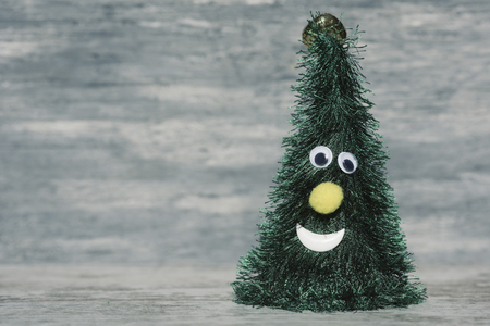 a christmas tree with a funny face against a gray rustic wooden background, with a blank space on the left Stock Photo