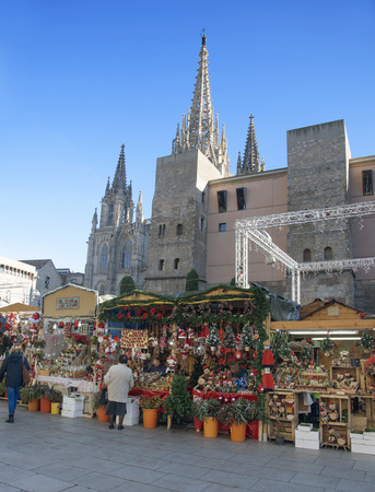BARCELONA, SPAIN - NOVEMBER 28, 2017: A view of the stalls of the Mercat de Santa Llucia, the popular Christmas market that is installed every year in front of the Cathedral during the holiday season Banco de Imagens - 92899831