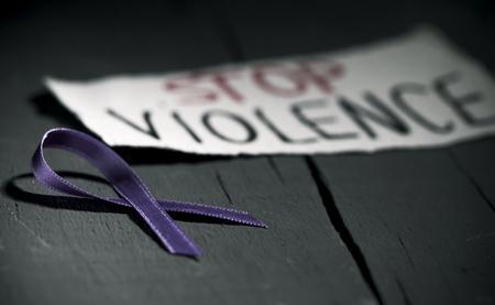 fioletowa wstążka dla świadomości o niedopuszczalności przemocy wobec kobiet i tekst zatrzymujący przemoc na kartce papieru, na ciemnoszarej rustykalnej drewnianej powierzchni