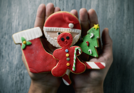 closeup of a young caucasian man with a pile of handmade christmas cookies with different shapes and colors in his hands, against a gray rustic wooden surface Foto de archivo