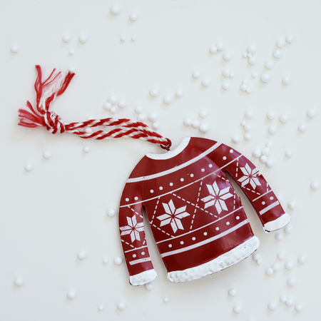 high-angle shot of a christmas ornament placed on a white surface sprinkled with small plastic balls simulating snow Stock Photo