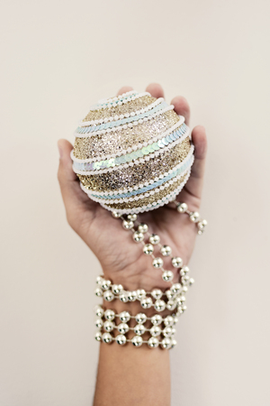 an elegant christmas ball in the hand of a young caucasian man ornamented with a silvery beaded garland 写真素材