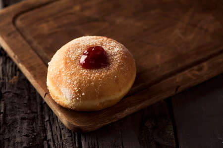closeup of a sufganiyah, a Jewish donut filled with strawberry jelly traditionally eaten on Hanukkah, on a rustic wooden table