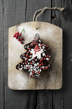 high angle shot of a chocolate cake in the shape of a christmas tree ornamented with star-shaped sprinkles and red berry-shaped dragees, placed on a wooden rustic table Banque d'images