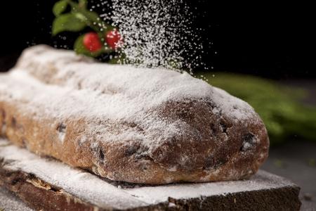 Nahaufnahme eines stollen Kuchens zur Weihnachtszeit besprüht mit dem Puderzucker, gesetzt auf eine hölzerne rustikale Tabelle