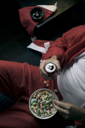 closeup of a young man wearing a santa suit drinking beer from a can and eting pop corn in bed Stock Photo
