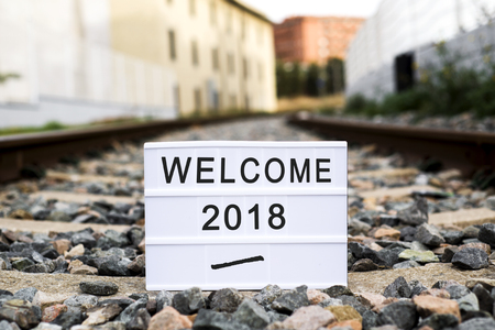 a lightbox with the text welcome 2018 placed on a railroad track, metaphor of the beginning of a new year as a journey