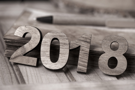 four wooden numbers forming the number 2018, as the new year, next to a rustic notepad with yellowish pages and a pen, on a rustic wooden table, in sepia toning Stock Photo