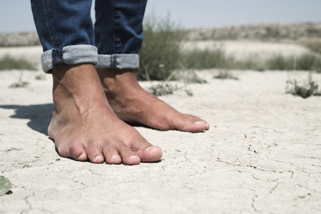 closeup of the bare feet of a young caucasian man on a cracked dry soil Stock Photo