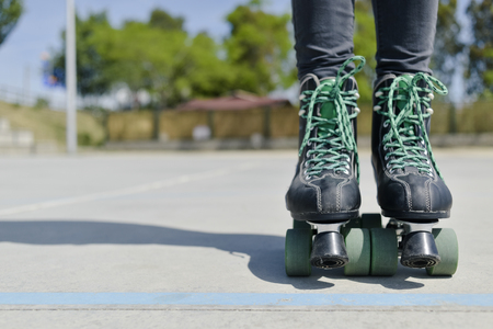 closeup of the feet of a young caucasian wearing quad skates outdoors, with a negative space on the left Foto de archivo
