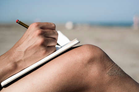 closeup of a young caucasian man writing with a pen in a notebook on his shaved legs, on the beach during the summer