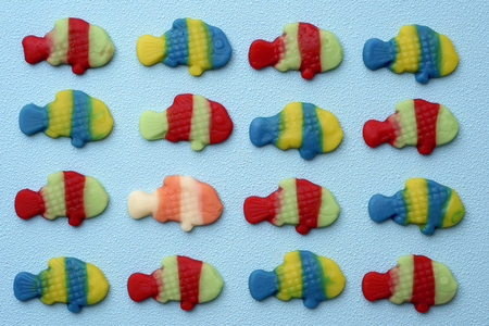 some fish-shaped gummy candies put in line on a blue background and a different one between them