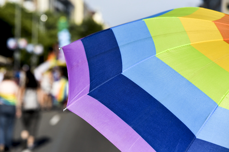 closeup of a rainbow-patterned umbrella in a pride parade