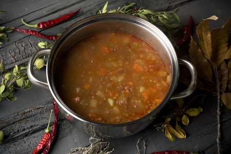 closeup of a stainless steel with a lentil stew on a gray rustic wooden table Banque d'images