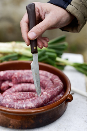 closeup of a young man piercing a raw pork meat sausage with the tip of a knife before to be cooked in a barbecue, and some calcots, sweet onions typical of Catalonia, Spain, in the background Banque d'images