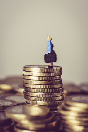 closeup of a miniature woman carrying a suitcase, on the top of a pile of euro coins, with some blank space on top