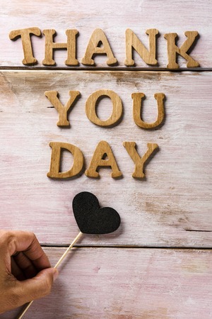some wooden letters forming the text thank you day on a rustic wooden surface and a heart attached to a stick in the hand of a young caucasian man