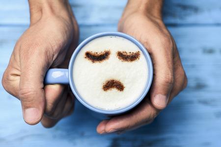 ujęcie pod dużym kątem młodego mężczyzny rasy kaukaskiej z niebieską filiżanką cappuccino o smutnej twarzy narysowanej kakao na mlecznej piance, na niebieskim rustykalnym stole