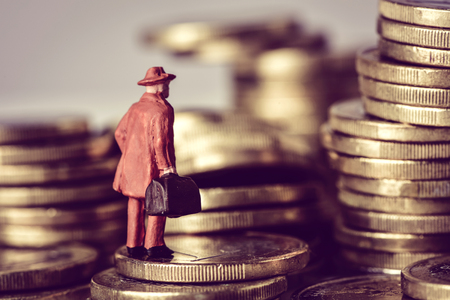 closeup of a miniature traveler man carrying a suitcase, on a pile of euro coins Archivio Fotografico
