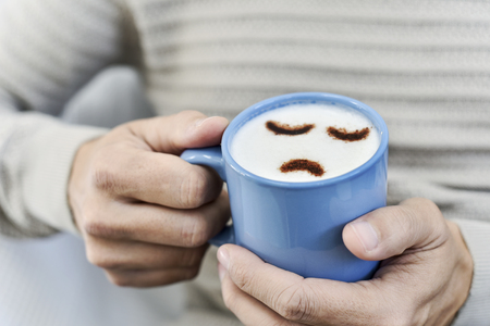 closeup a young caucasian man with a blue cup of cappuccino with a sad face drawn with cocoa powder on the milk foam