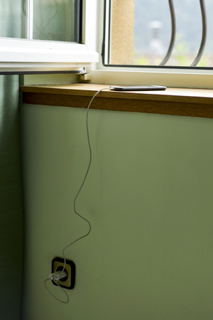 a smartphone, on a window sill indoors, being charged plugged to a socket Banque d'images
