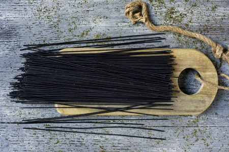 high angle view of a bunch of uncooked black spaghetti on a wooden chopping board, placed on a gray rustic wooden table Banque d'images