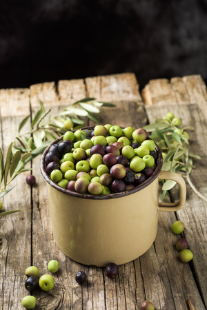 a handled enamelware pot full of arbequina olives from Catalonia, Spain, on a wooden rustic table, against a dark background with a blank space on top Banque d'images