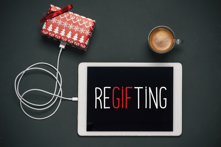 high-angle view of a tablet with the word regifting in its screen, connected to a gift by a cable, and a cup of coffee, placed on a dark gray table Banque d'images