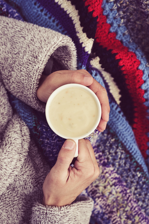 high-angle view of an ill young caucasian man at home wearing a fluffy house robe and wrapped in a colorful knitted blanket, warming up with a cup of hot soup