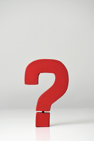 a red three-dimensional question mark on an off-white background, with a blank space on top Stock Photo