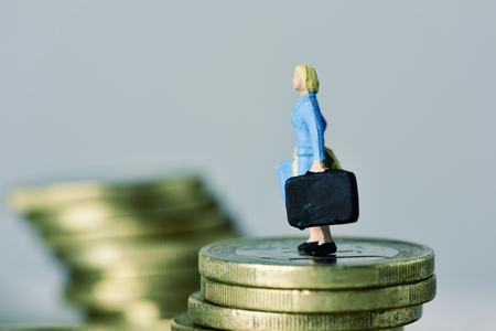 closeup of a miniature woman carrying a suitcase, on the top of a pile of euro coins, with some blank space around her Stockfoto