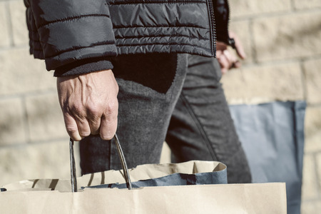 closeup of a young caucasian man carrying some paper shopping bags with his purchases on the street