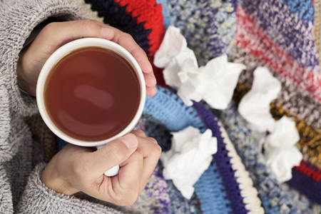 high-angle view of an ill young caucasian man at home wearing a fluffy house robe and wrapped in a colorful knitted blanket, warming up with a cup of hot tea