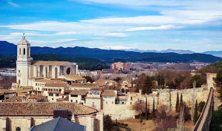 an aerial view of the Old Town of Girona, in Spain, seen from above highlighting the bell tower of the Cathedral and the Canigou Mountain snowcapped in the background Banque d'images