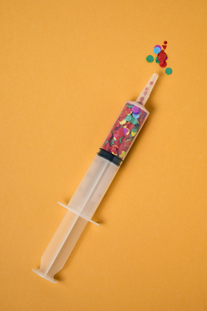 high-angle view of a syringe full on confetti on an orange background with some blank space around it