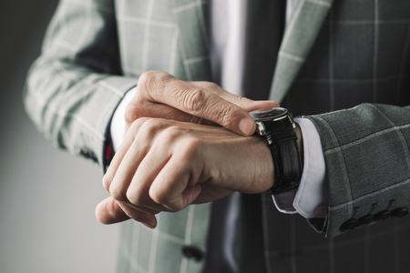 closeup of a young businessman wearing an elegant gray suit adjusting his wristwatch