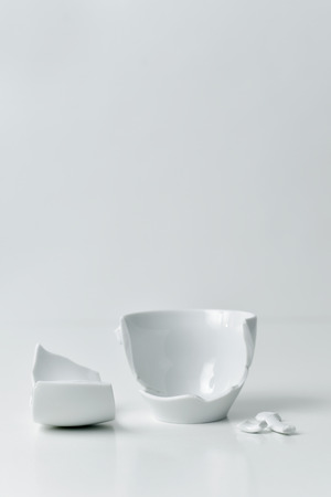 a broken white ceramic coffe cup with its pieces spread out on a white table, against a white background with a blank space on top
