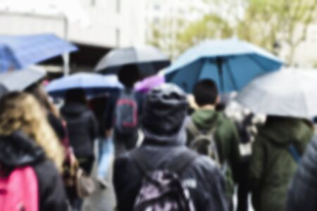 a defocused blur background of people walking under the rain protected by umbrellas in a street of a city