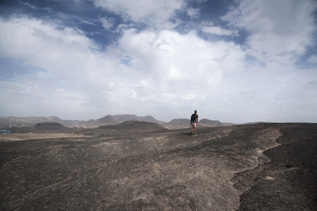 a young caucasian man, seen from behind, carrying a backpack walking by a volcanic landscape in Fuerteventura, Canary Islands, Spain