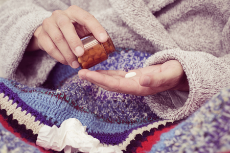 closeup of an ill young caucasian man at home wearing a fluffy house robe and wrapped in a colorful knitted blanket, taking a pill out from a bottle