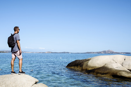 a young caucasian man, seen from behind, carrying a backpack observing the sea in the Costa Smeralda, in Sardinia, Italy, with a large blank space in the sky