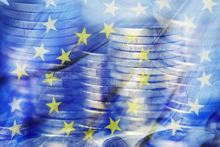 Eine Mehrfachbelichtung einiger Haufen von Euro-Münzen und einer Flagge der Europäischen Union Standard-Bild - 93436719