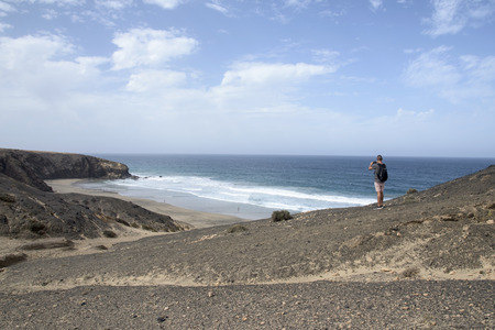 a young caucasian man, seen from behind, carrying a backpack taking a picture with his smartphone of the Viejo Rey Beach in Fuerteventura, Canary Islands, Spain Banque d'images