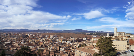 a panoramic view of Girona, in Spain, seen from above highlighting the bell tower of the Cathedral and the Canigou Mountain snowcapped in the background